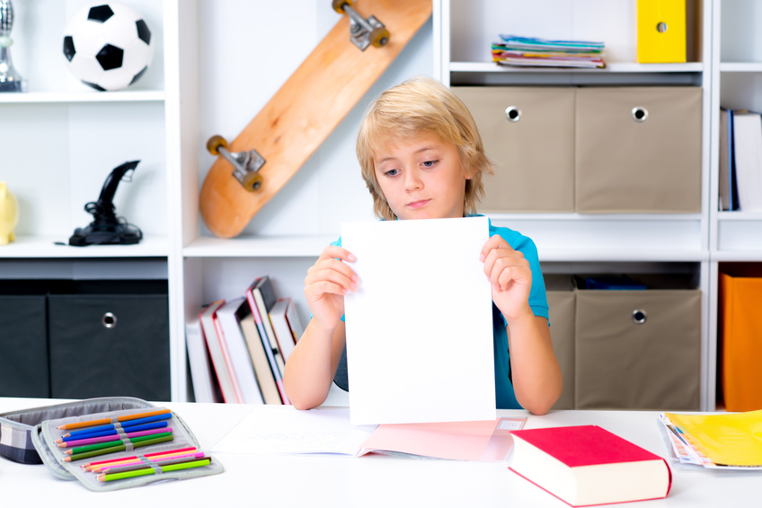 blond boy on desk with bad report card